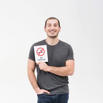 Улыбается портрет человека, показывающего знак не курить с рукой в кармане на белом фоне