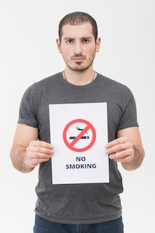 白い背景に対して立っていない禁煙の標識を保持している若い男の肖像