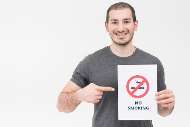 笑顔の若い男が白い背景で隔離の禁煙サインに向かって指を指す