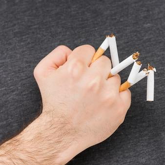 彼の拳で壊れたタバコを持っている人の手のクローズアップ