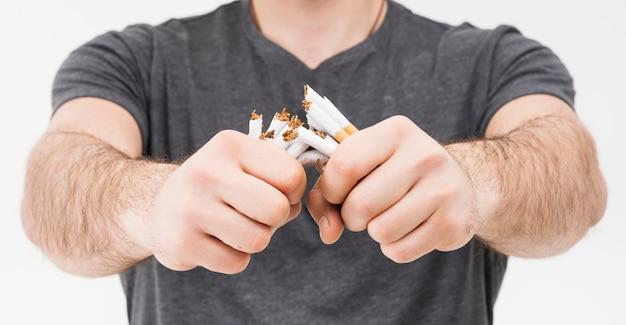 Панорамный вид улыбающегося человека ломать сигареты двумя руками