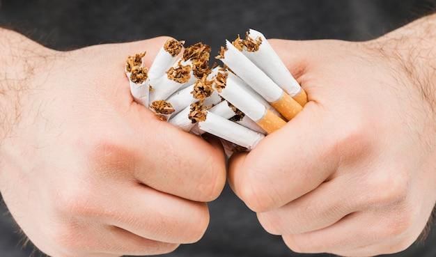 タバコの束を壊す手のクローズアップ
