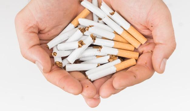白い背景に分離された壊れたタバコを持っている人間の手のクローズアップ