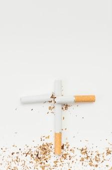 Вид сверху крест знак из сломанной сигареты на белом фоне