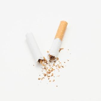Сломанная сигарета и табак на белом фоне