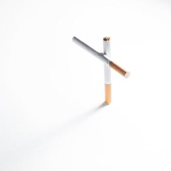 Вид сверху на крест знак из сигареты на белом фоне