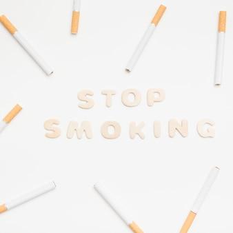 白い背景に対してタバコに囲まれたテキストの喫煙をやめる
