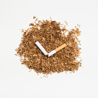 Высокий угол обзора табака и сломанной сигареты на белой поверхности