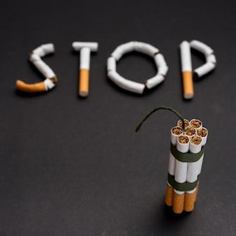 黒の背景上の芯とタバコの束を持つタバコから作られたぼやけたテキストストップ
