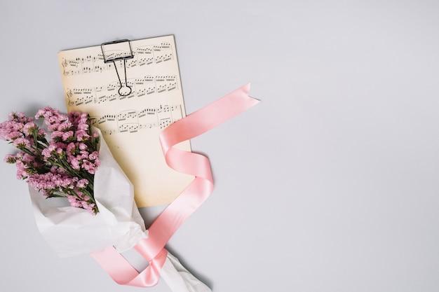 ライトテーブルの上の楽譜と花の花束