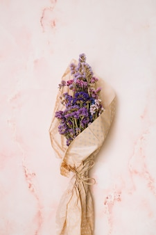 Букет цветов в упаковке бумаги на мраморном столе