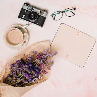 コーヒーカップ、カメラとテーブルの上のグラスを持つ空白のノートブック