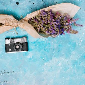 青いテーブルの上のカメラと花の花束