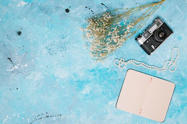 カメラ、ノートブックと青いテーブルの上のビーズの花枝