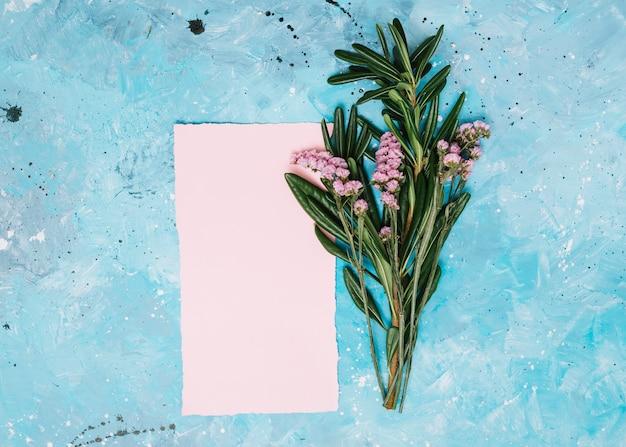 Цветочные ветки с чистого листа на синем столе