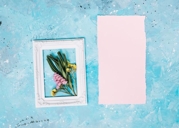Маленькие цветы ветви в рамке с чистого листа на столе