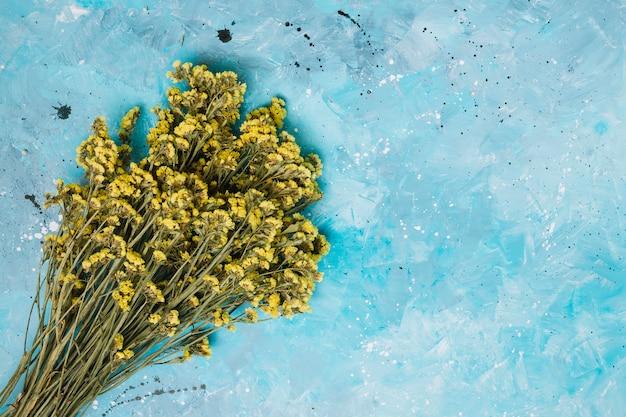 青いテーブルの上の大きな黄色い花ブーケ