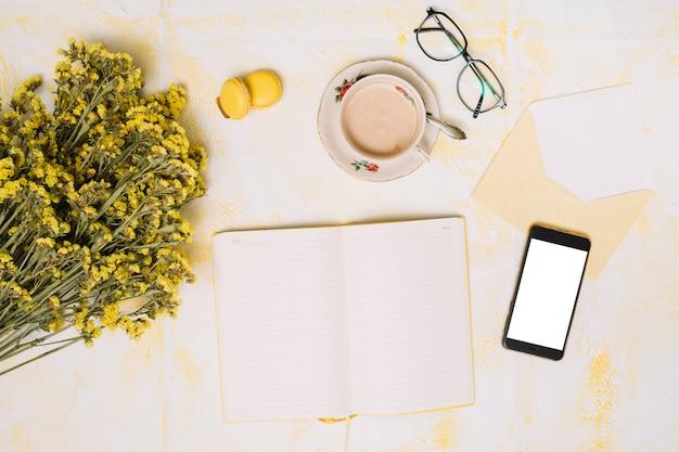 スマートフォン、コーヒー、テーブルの上のノートと花の花束