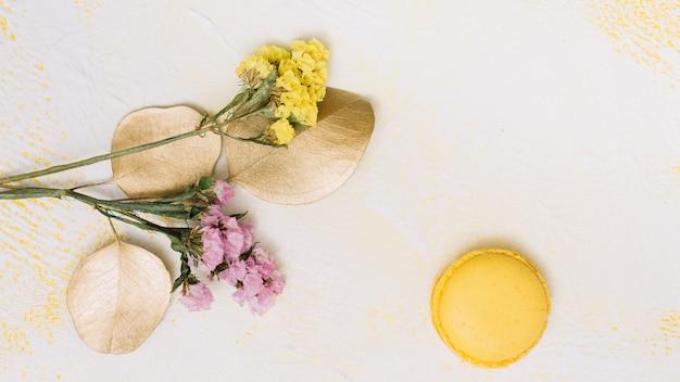白いテーブルの上のクッキーと小さな花枝