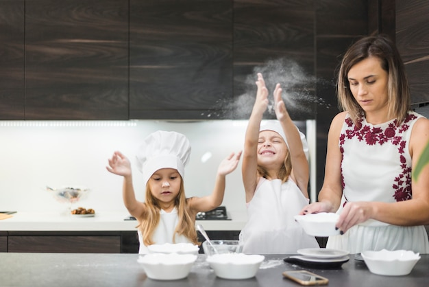 母親が食べ物を準備しながら台所で楽しんでいるかわいい女の子