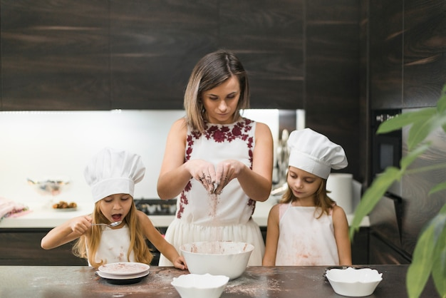 Мама смешивает какао-порошок для приготовления печенья со своими дочерьми на кухне
