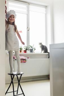 シェフの帽子と自宅のテーブルの上にエプロン立っているで乱雑な少女の笑顔