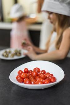 キッチンカウンターの上の白いボウルにウェットトマトのクローズアップ