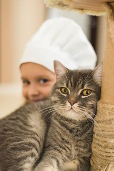 小さな女の子の笑顔の前に猫のクローズアップ