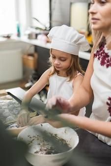 母と娘の台所でクッキーを準備します。