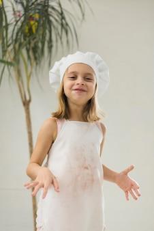 白いエプロンとシェフの帽子をかぶっている笑顔の女の子