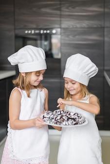 彼女の妹に焼きたてのクッキーを示すかわいい女の子