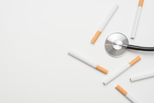 背景に分離されたタバコと聴診器のオーバーヘッドビュー