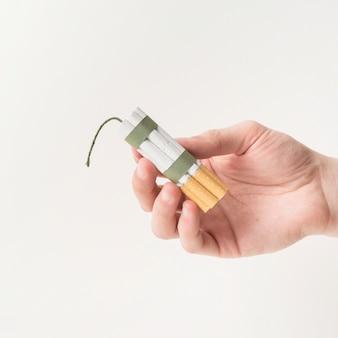 ロープと芯で結ばれたタバコを持っている人間の手のクローズアップ