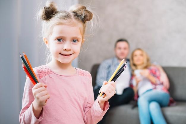 Милая маленькая девочка, показывая красочный рисунок карандашами
