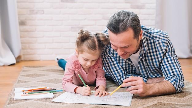 幸せな父と娘が家で一緒に描いています。