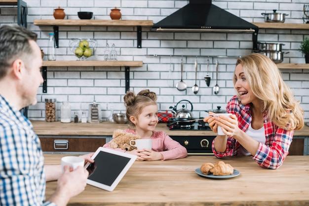 Веселые родители и дочь наслаждаются завтраком на кухне