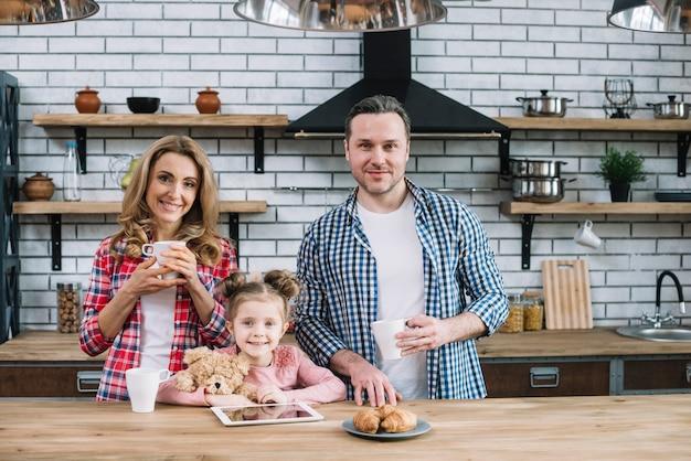 台所で朝食を食べて笑顔の家族の正面図