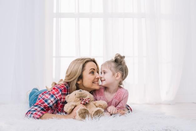 美しい母親と娘のテディベアと変な顔を作る毛皮の上に横たわる