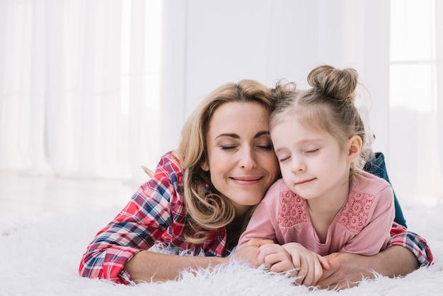 Улыбающаяся мама обнимает своего невинного ребенка
