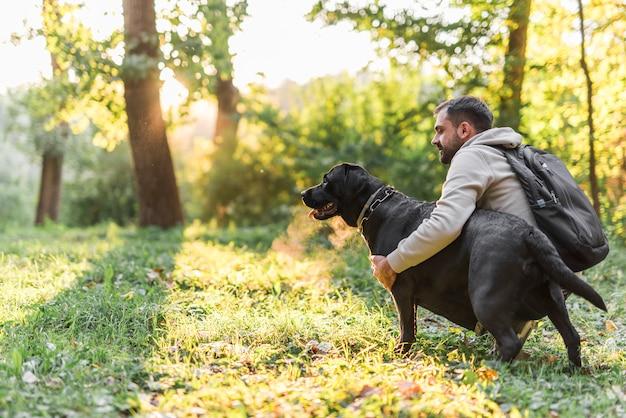 若い男が庭で彼のペットの犬を保持
