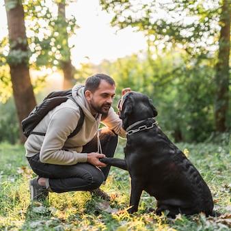 公園で彼の犬を持つ若い男