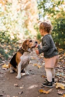 Маленькая девочка кормит своего питомца в лесу
