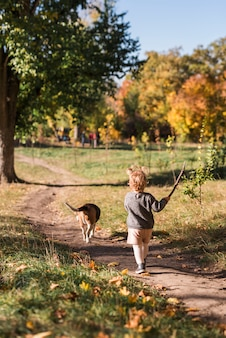 森林歩道で彼女のペットの犬を連れて歩いて小さな女の子の背面図