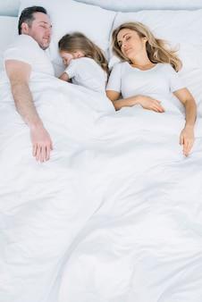 子供と両親がベッドで寝ている