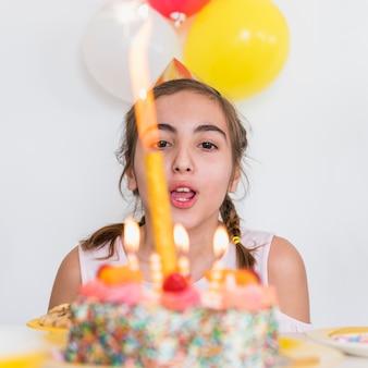 パーティーでおいしい誕生日ケーキのろうそくを吹きかわいい女の子のクローズアップ