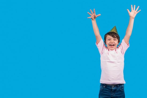 青い表面の前で手を上げて興奮している少年