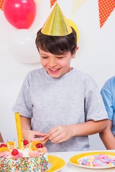 Крупным планом счастливого мальчика, глядя на красочный торт ко дню рождения