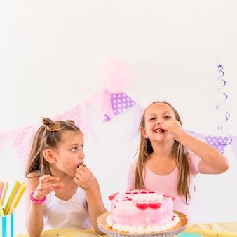 テーブルの上のおいしいケーキの前でイチゴを食べる二人の少女