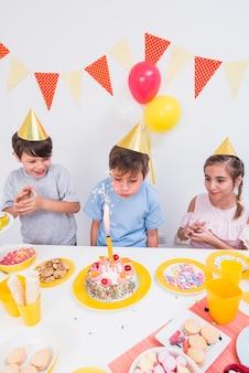 ケーキの後ろに立っている彼の友人とキャンドルを吹いて誕生日少年