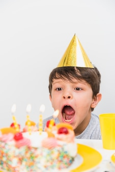パーティーハットを着て誕生日の蝋燭を吹く少年のクローズアップ